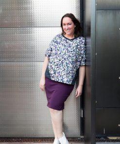 Model lehnt an der Wand und trägt einen gemusterten Pullover und violetten Rock