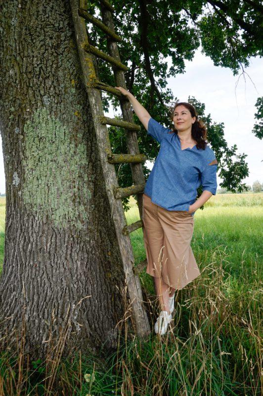 Model hält sich an einer Leiter an. Sie trägt eine blaue Bluse und sandfarbenen Hosenrock.